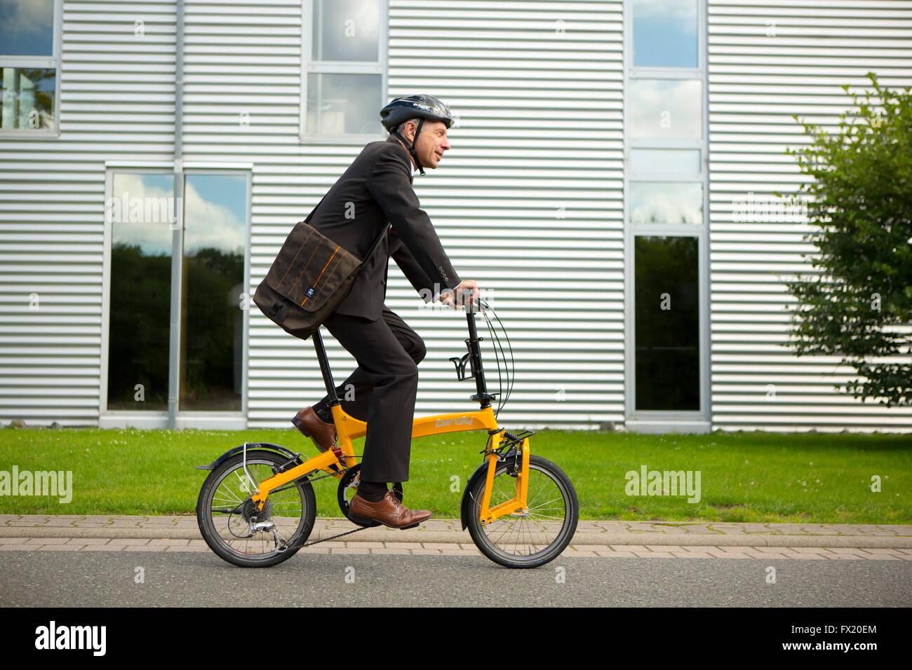 Geschäftsmann mit Helm Reiten ein Faltrad zu arbeiten Stockbild