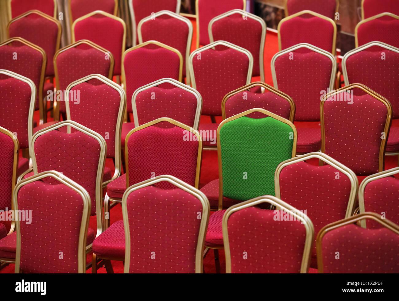 Vielfalt, verschiedene und einzigartige Konzept - grünen Stuhl in einer Gruppe von roten Stockbild