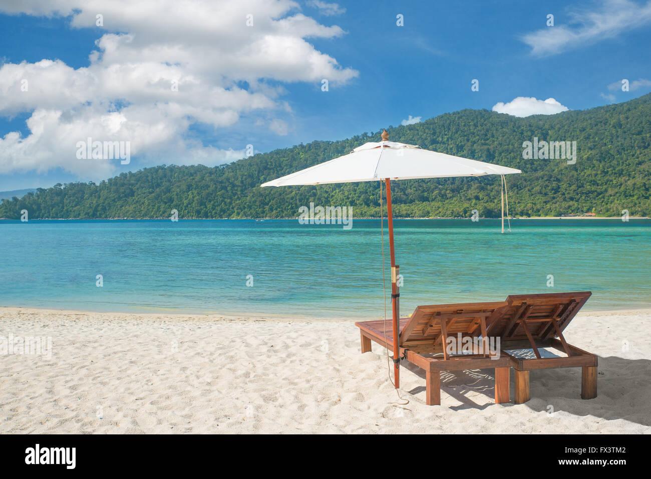 Sommer, Reisen, Urlaub und Ferien-Konzept - Liegestühle und Sonnenschirm am Insel Phuket, Thailand Stockbild