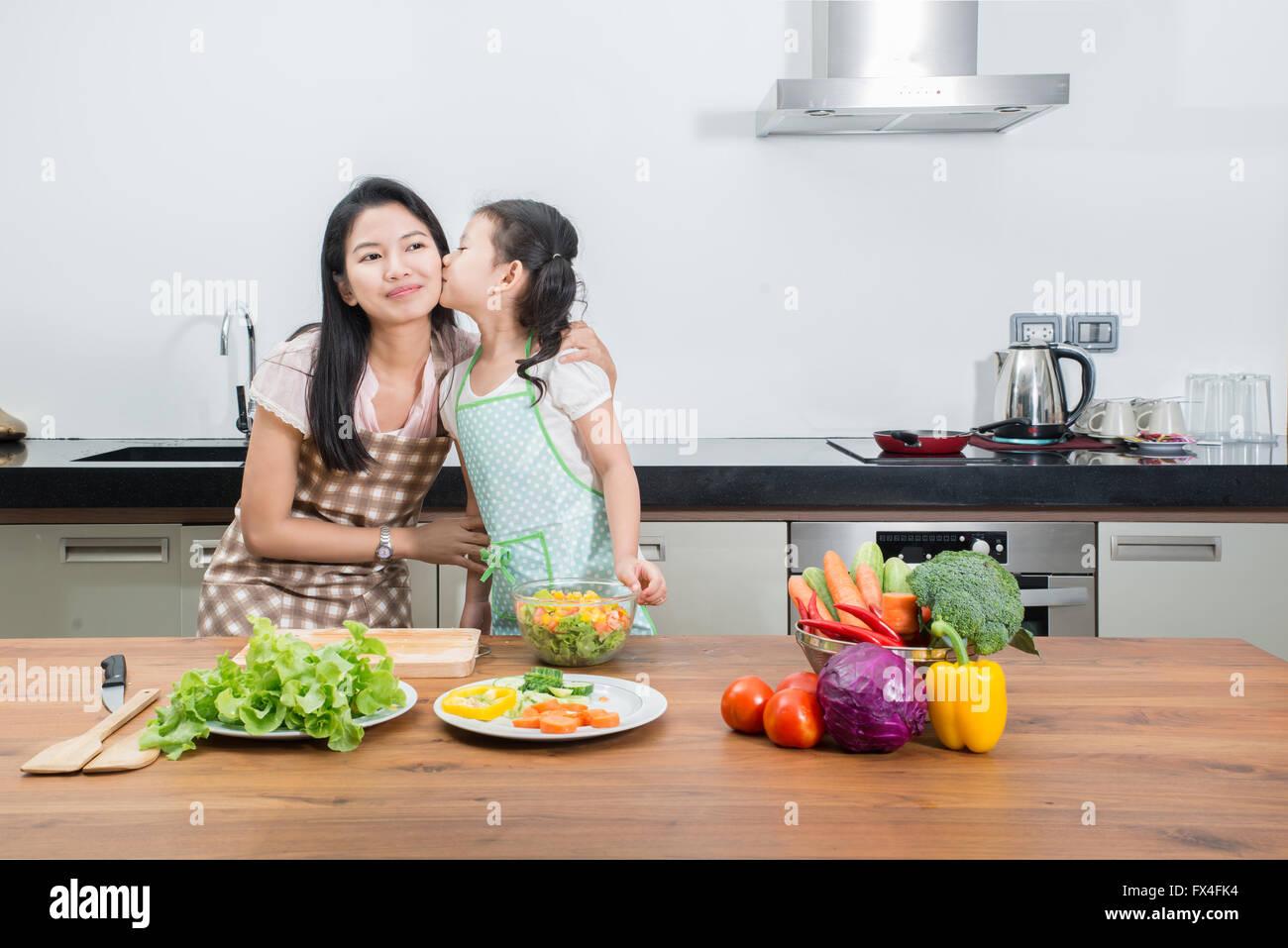 Familie, Kinder und glückliche Menschen Konzept - Asiatisch Kochen in der Küche zu Hause Tochter von Mutter Stockbild