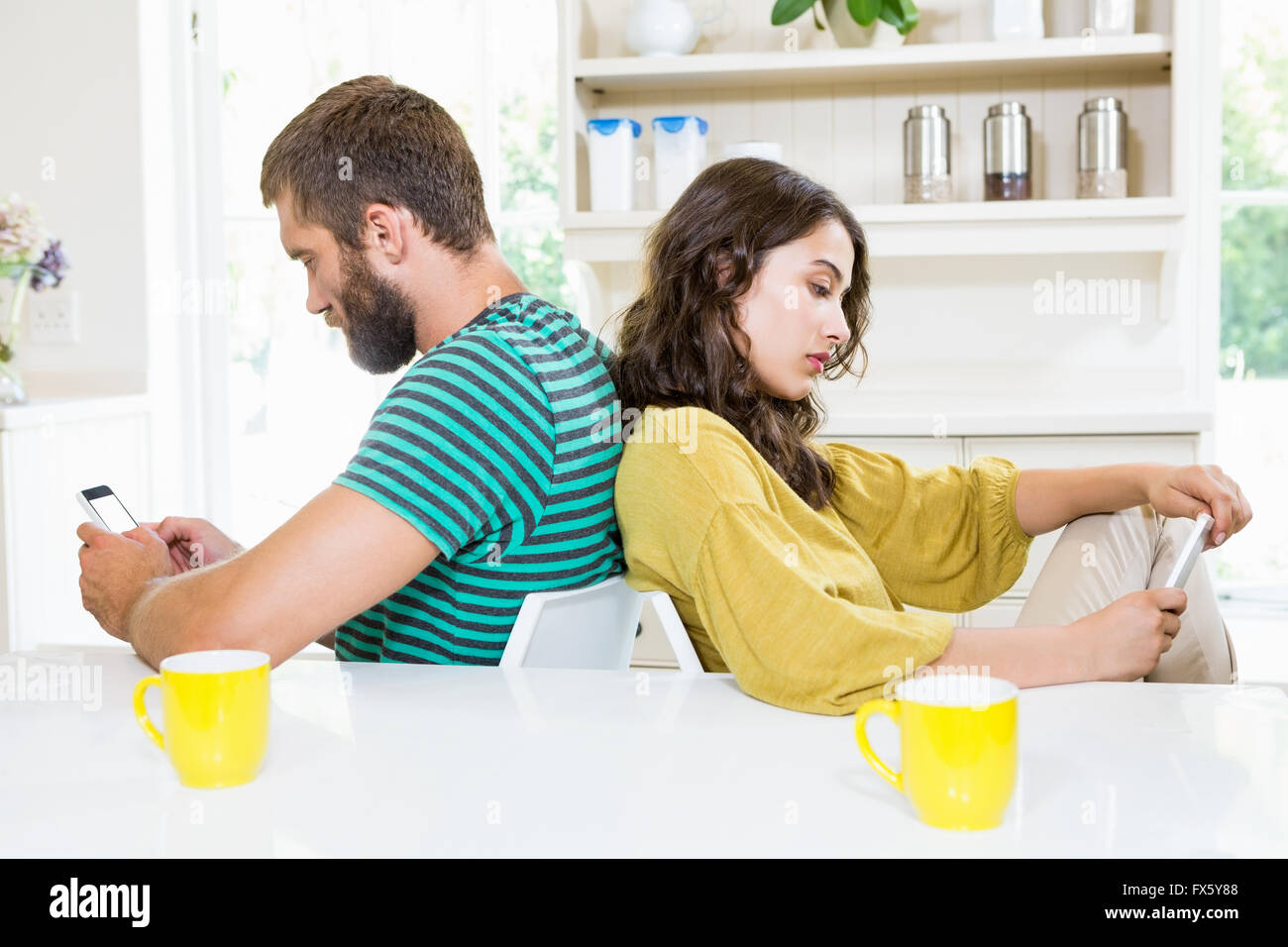 Paar sitzen Rücken an Rücken und Text messing auf Handy Stockfoto
