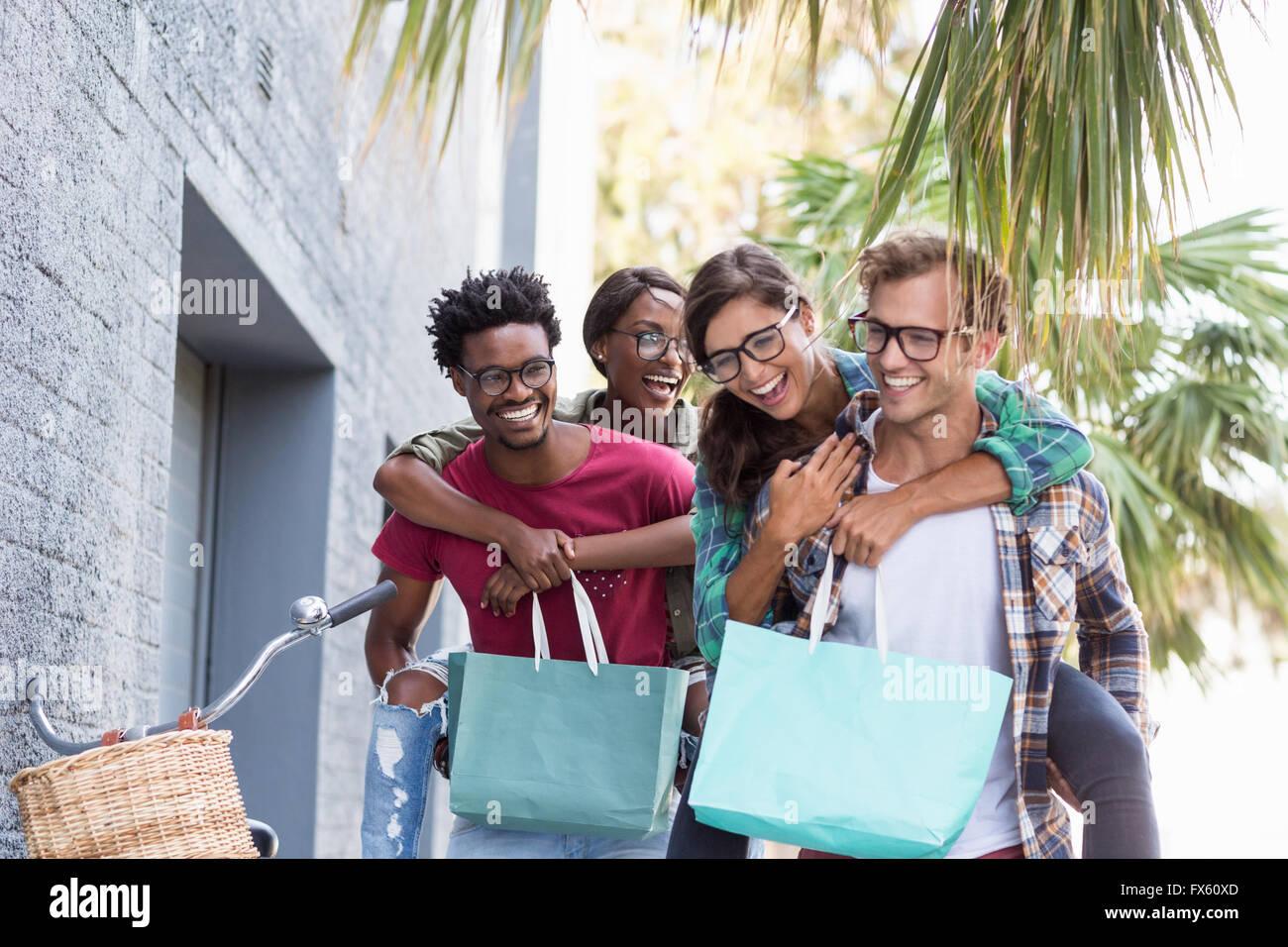 Junge Männer geben Frauen Huckepack Stockbild