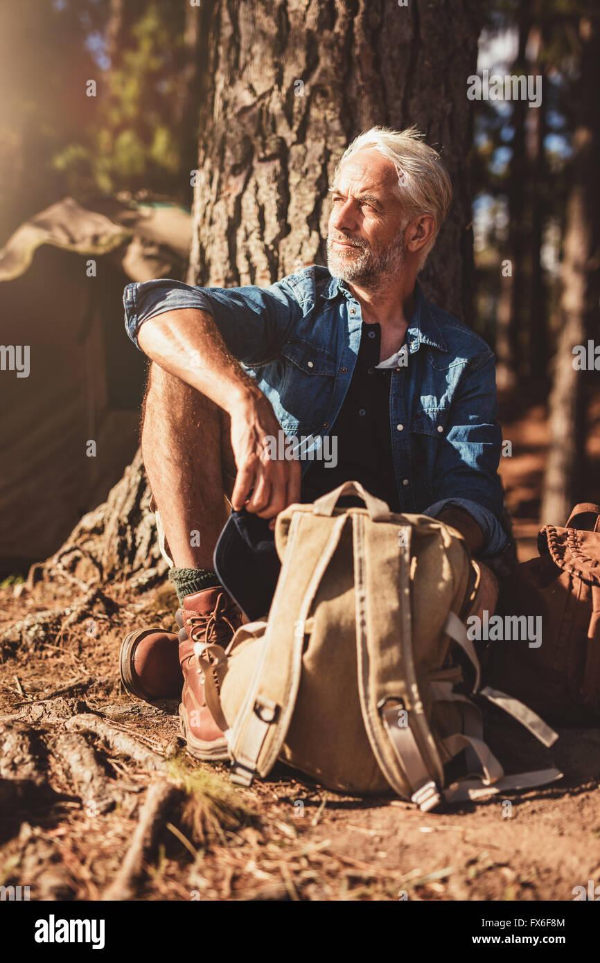 Portrait von senior Mann wegsehen von einem Baum sitzend. Älteren Mann mit einem Rucksack im Freien an einem Stockbild