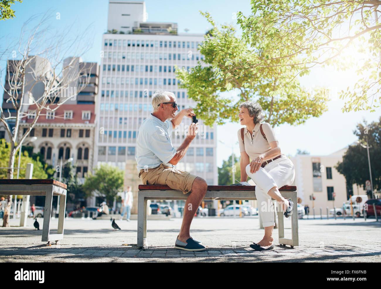 Ältere Mann die Fotos von seiner Frau. Ältere Paare, die Spaß im Urlaub. Stockbild