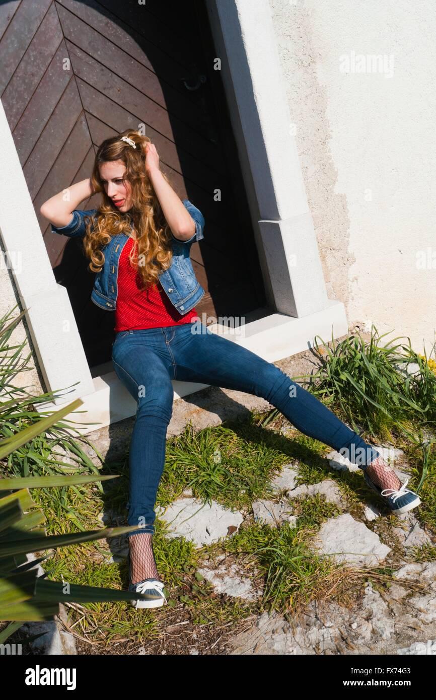 Junge Frau In Jeans Hosen Sitzen Sitzen Sitzen Vor Der Tür