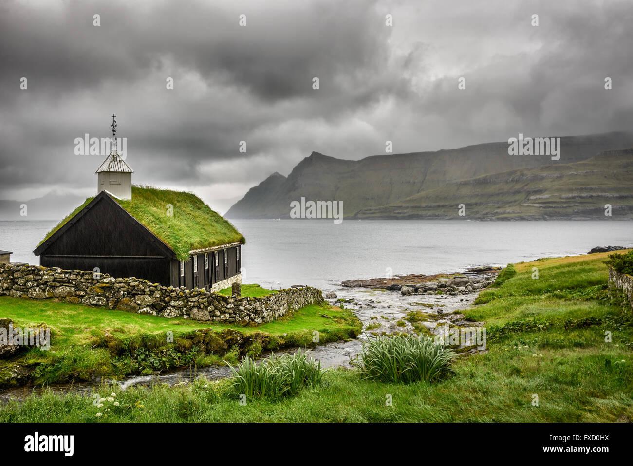 Kleine Dorfkirche in Funningur unter schweren Wolken. Funningur befindet sich auf der Insel Eysturoy, Färöer, Stockbild