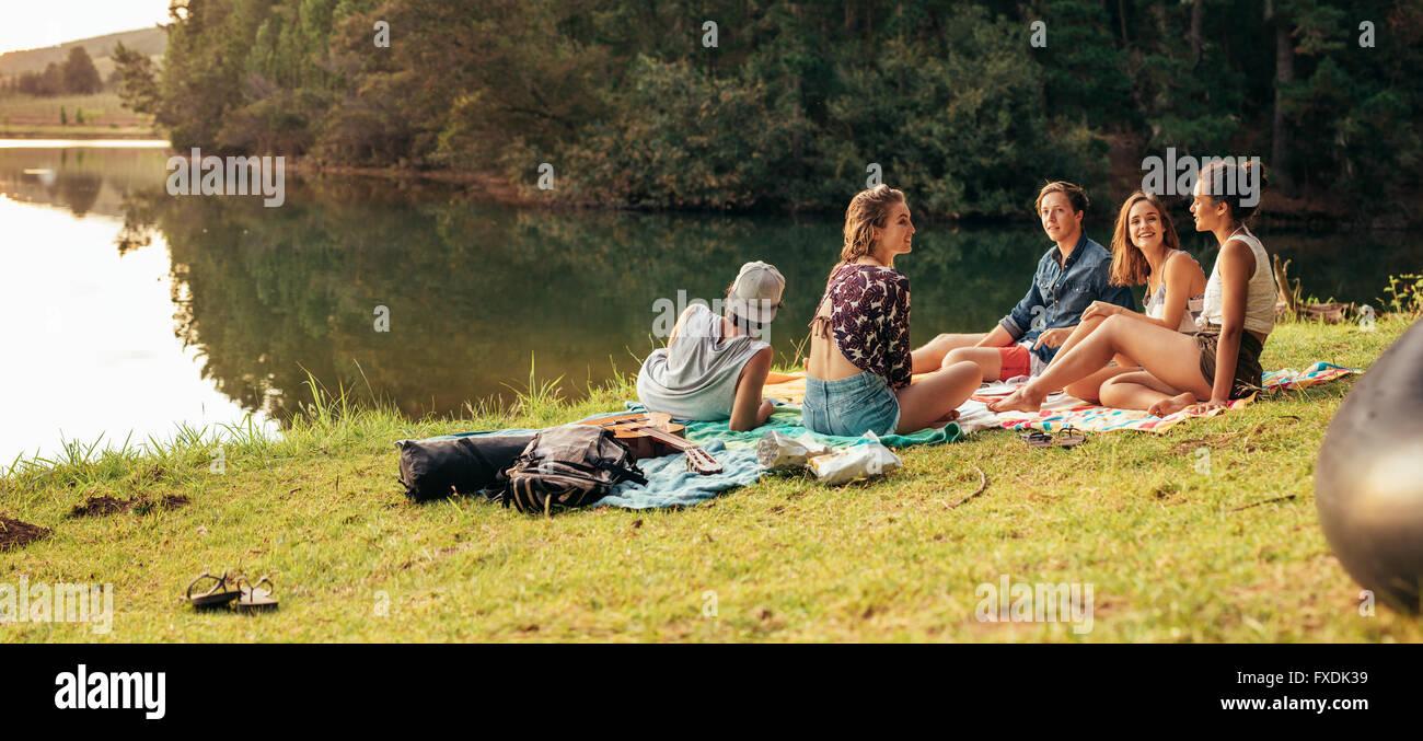 Junge Freunde mit Picknick am Ufer eines Sees. Junge Freunde, einen Tag am See zu genießen. Stockbild
