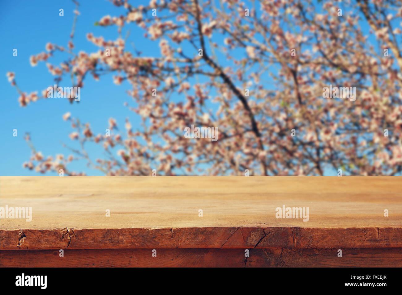 rustikaler Holztisch vor Frühjahr weiße Kirschblüten Baum. Vintage gefilterten Bild. Produkt anzeigen Stockbild