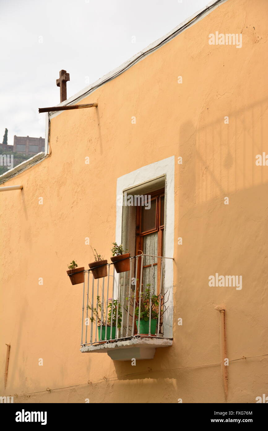 Gelbes Haus mit weiß gerahmten Fenster und einen kleinen Balkon mit ...