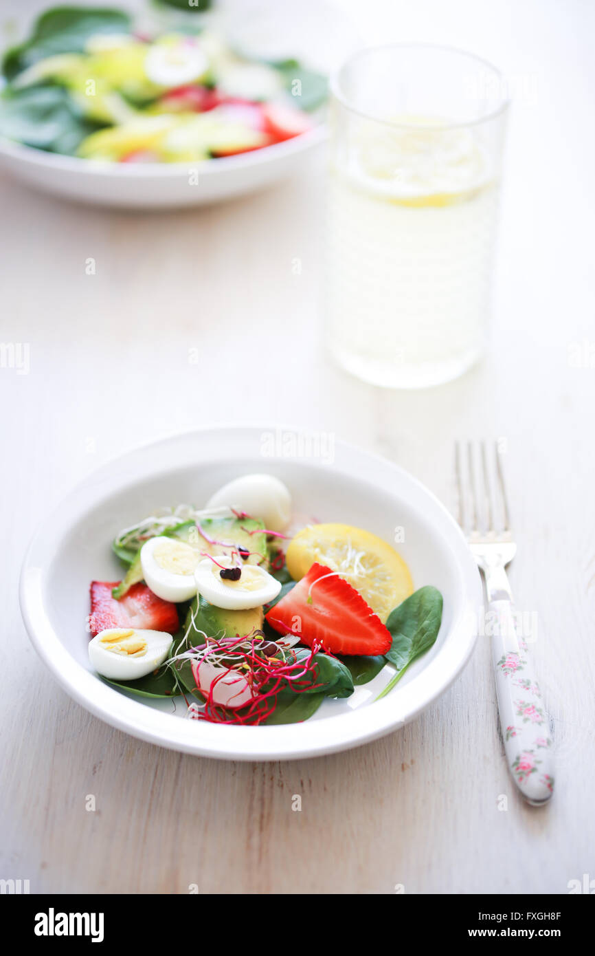 Baby-Spinat, Avocado, Zitrone, Erdbeeren und Wachtel-Eiern-Salat Stockbild