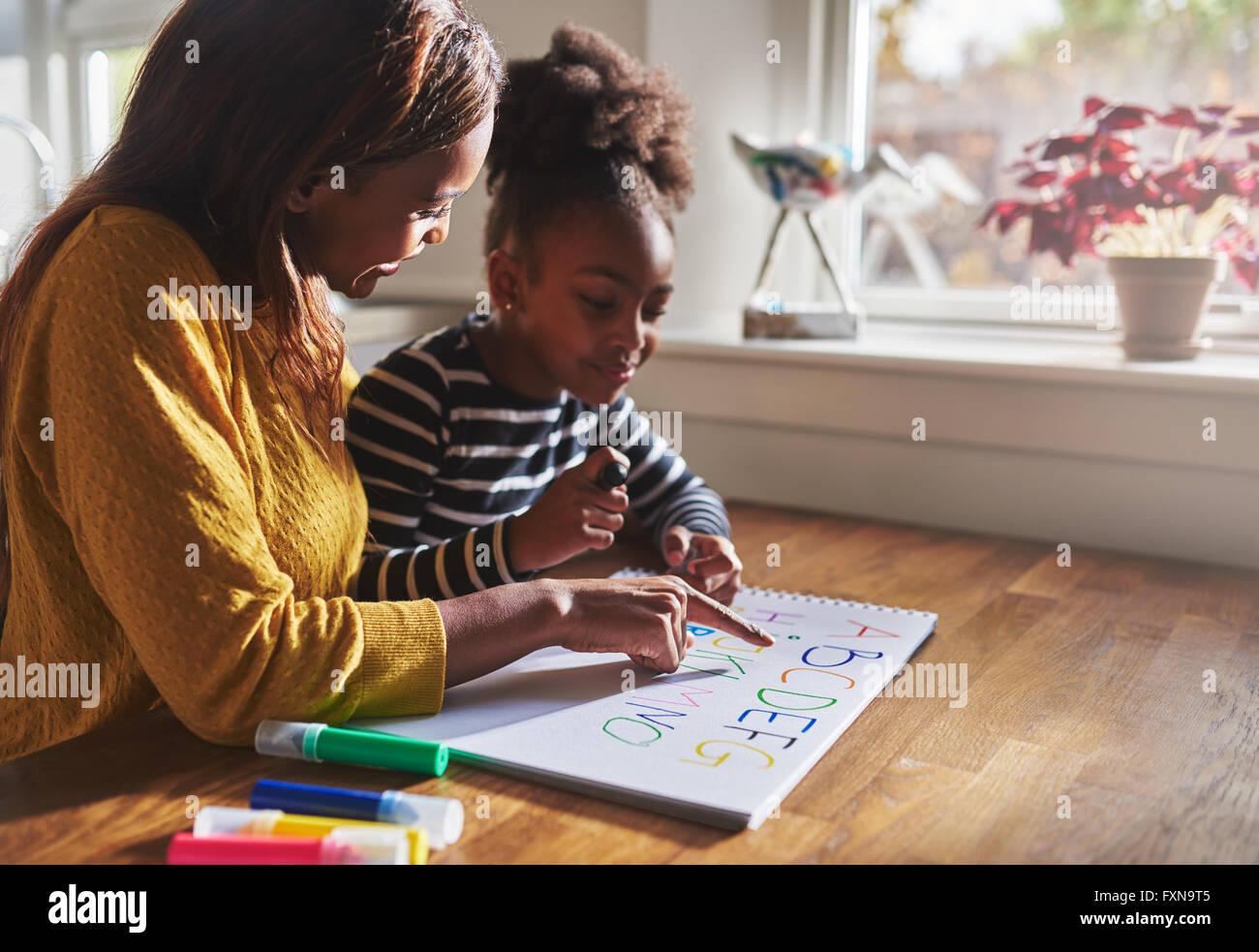 Frau und Kind zu Hause, Alphabet lernen schwarze Mutter und Tochter Stockbild