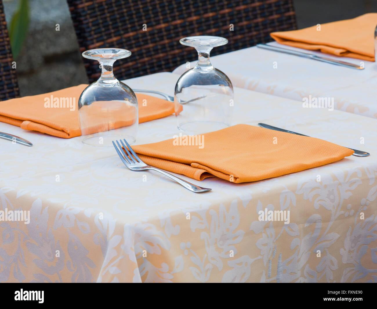 Tisch im Restaurant zubereitet mit Damast Tischdecke, orange Serviette, Besteck und Gläser Stockbild