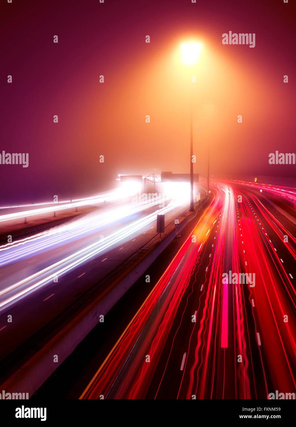 Viel befahrenen Autobahn Ampel Wanderwege in einer nebligen Nacht Highway 401, Toronto, Ontario, Kanada Stockbild