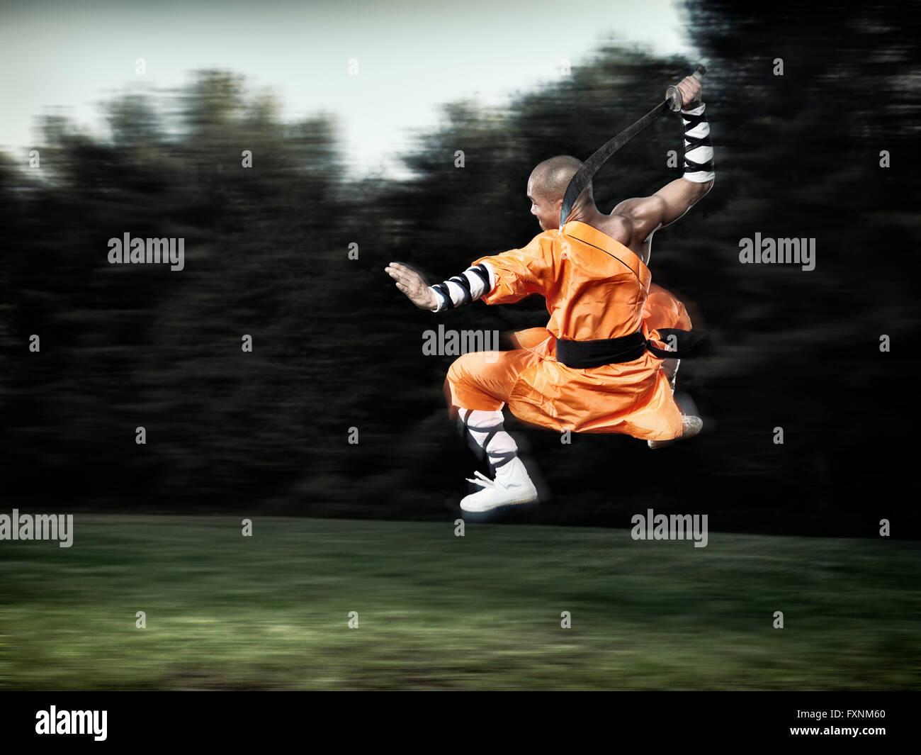 Shaolin-Krieger-Mönch in der Luft springen mit einem breiten Schwert Stockbild