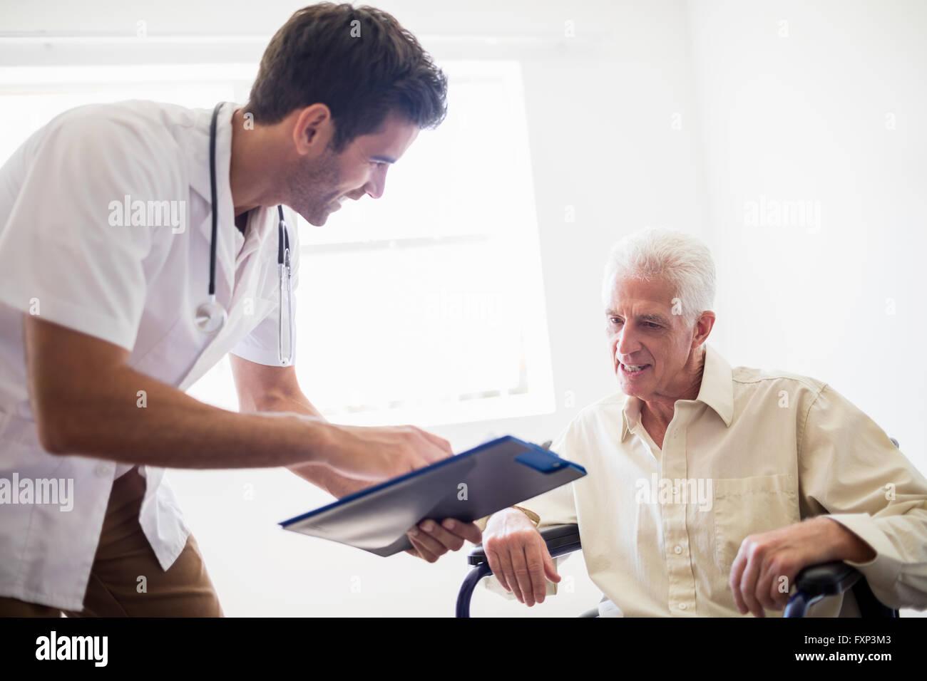 Krankenschwester zeigt senior Mann ein Dokument Stockbild