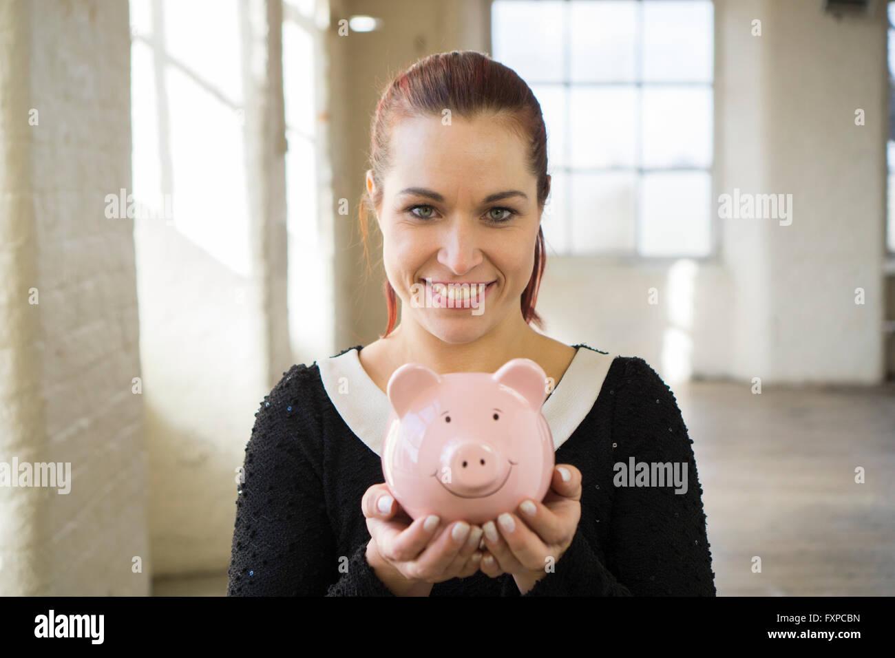 Glückliche Frau hält ein Sparschwein lächelnd Stockbild