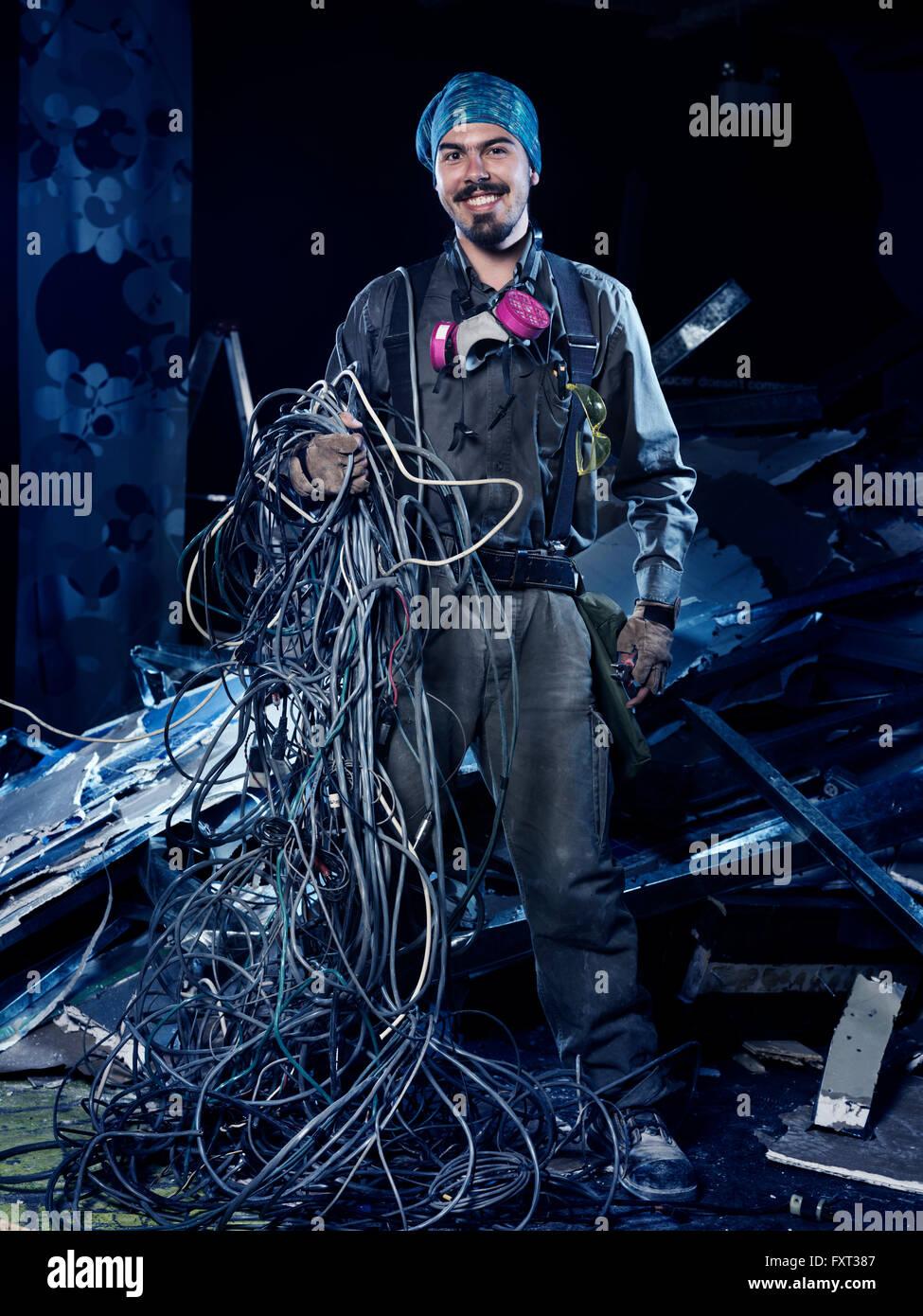 Elektroinstallateur bei der Arbeit, lächelnd, mit einem Bündel von Drähten, künstlerische Porträt Stockbild
