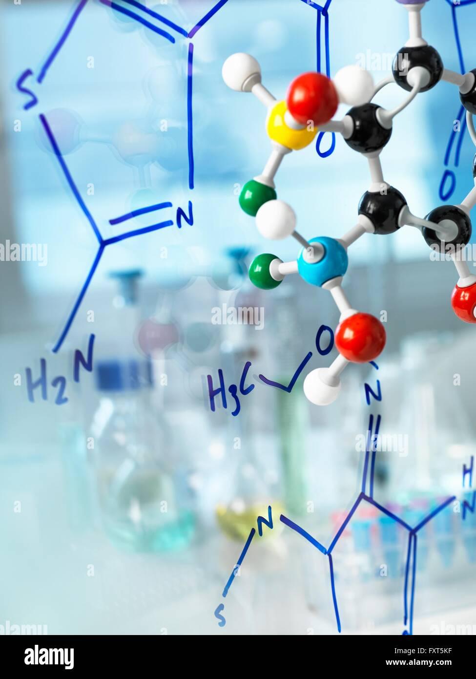 Ball und Stock Molekülmodell mit Formel des neuen Medikaments geschrieben am Glas Stockbild