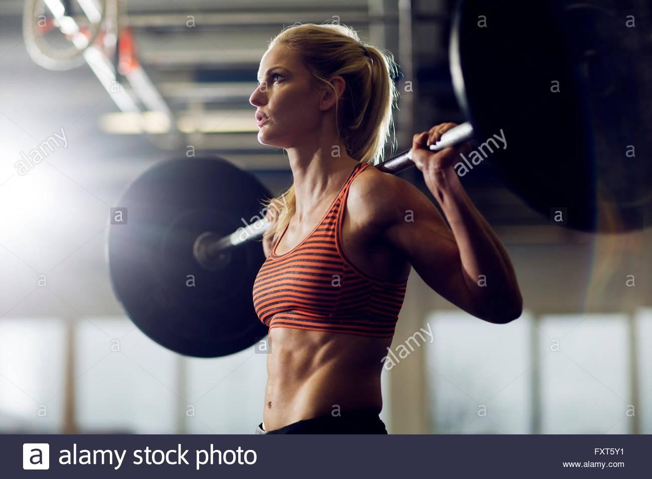 Mitte Erwachsene Frau heben Langhantel auf Schultern in Turnhalle Stockbild
