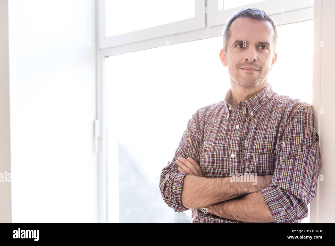 Reifer Mann Check Hemd gelehnt Fenster Arme gekreuzt aussehende Weg Lächeln Stockfoto