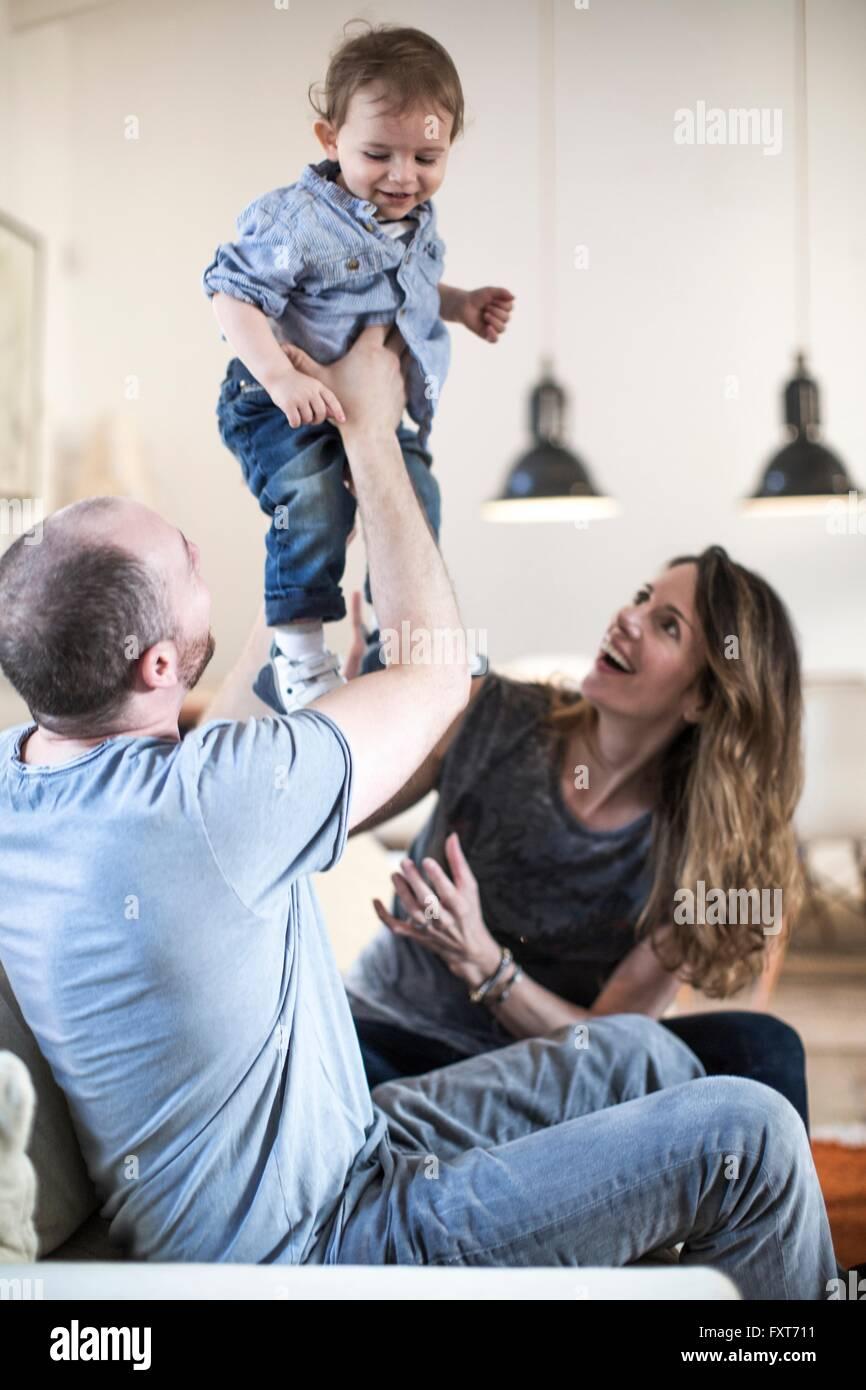 Eltern, die lächelnd Babyjungen hochhalten Stockbild