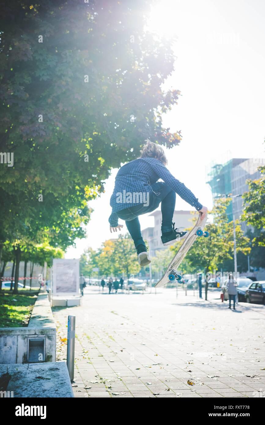 Junge männliche Skater Skateboard Sprung auf Bürgersteig zu tun Stockbild