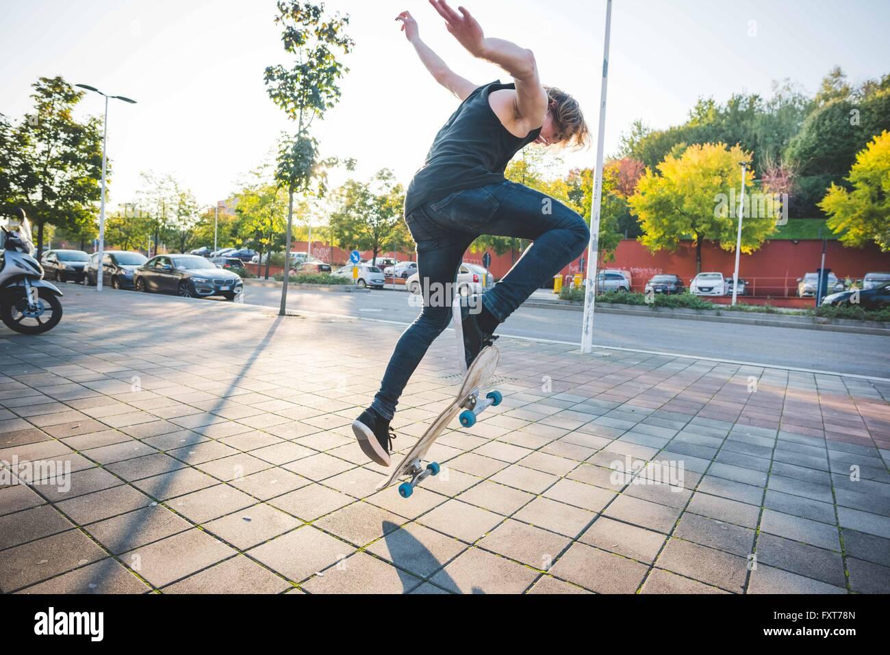 Junge männliche urban Skater tun Skateboard Sprung-Trick auf Bürgersteig Stockbild