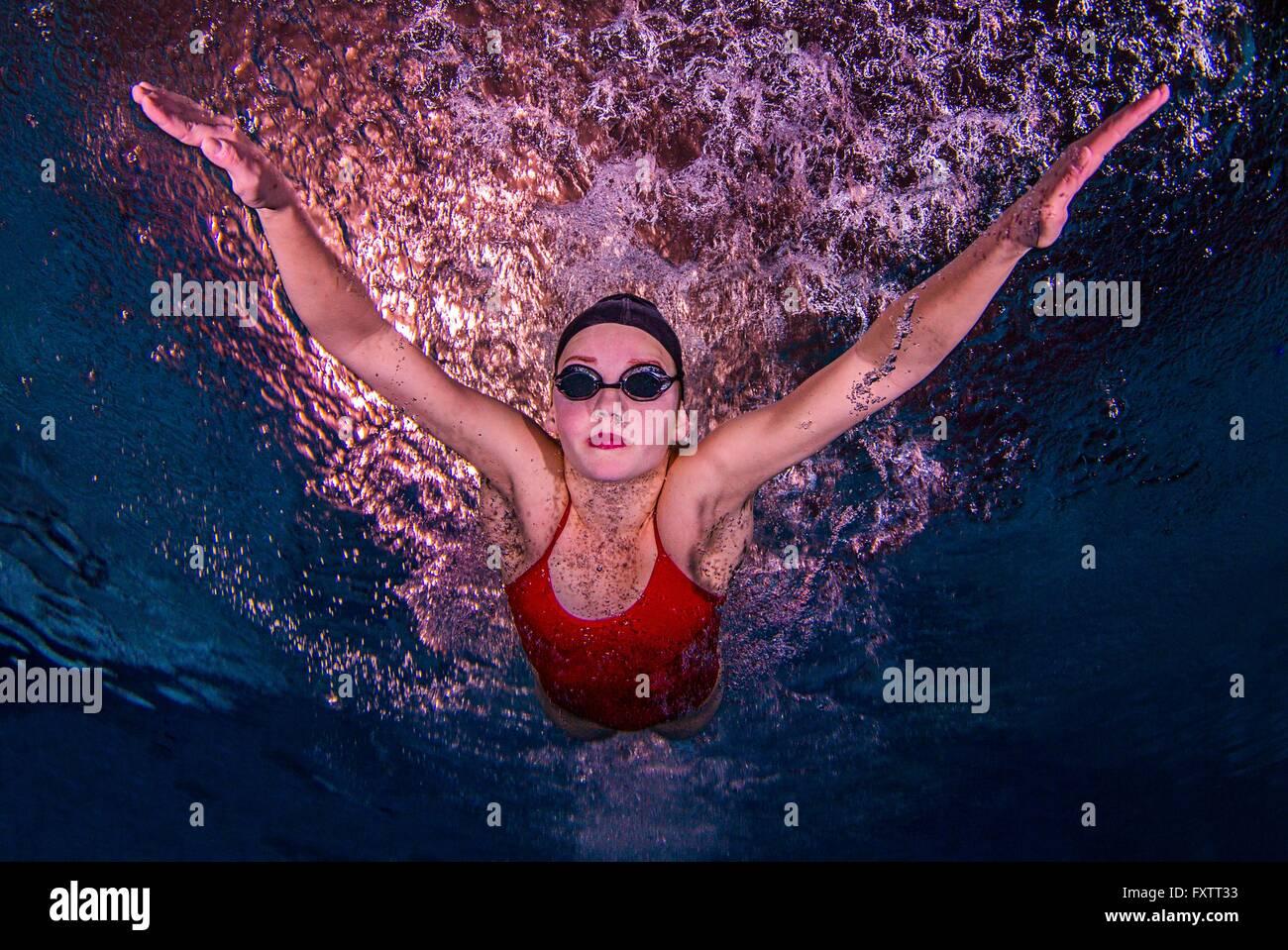 Junge Frau, die unter Wasser schwimmen Stockbild
