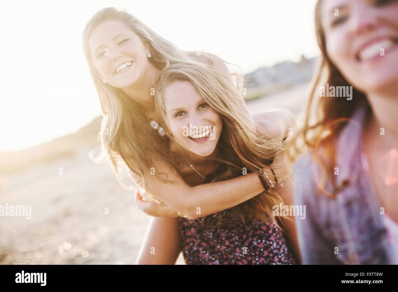 Frau am Strand geben Freund Huckepack Blick auf die Kamera zu Lächeln Stockbild