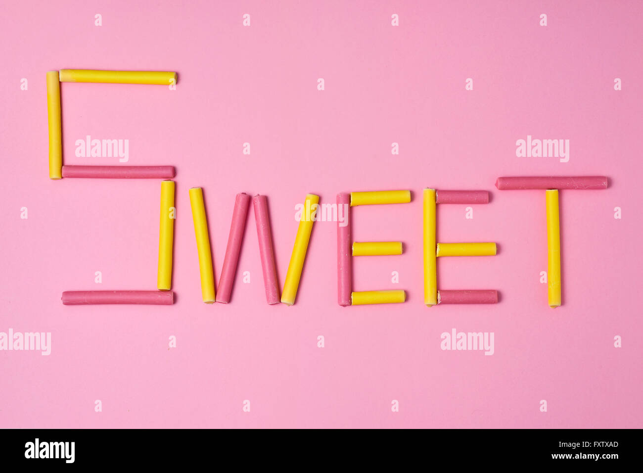 gelb und rosa beschichtet Marshmallows bilden die Wort süß auf einem rosa Hintergrund Stockbild