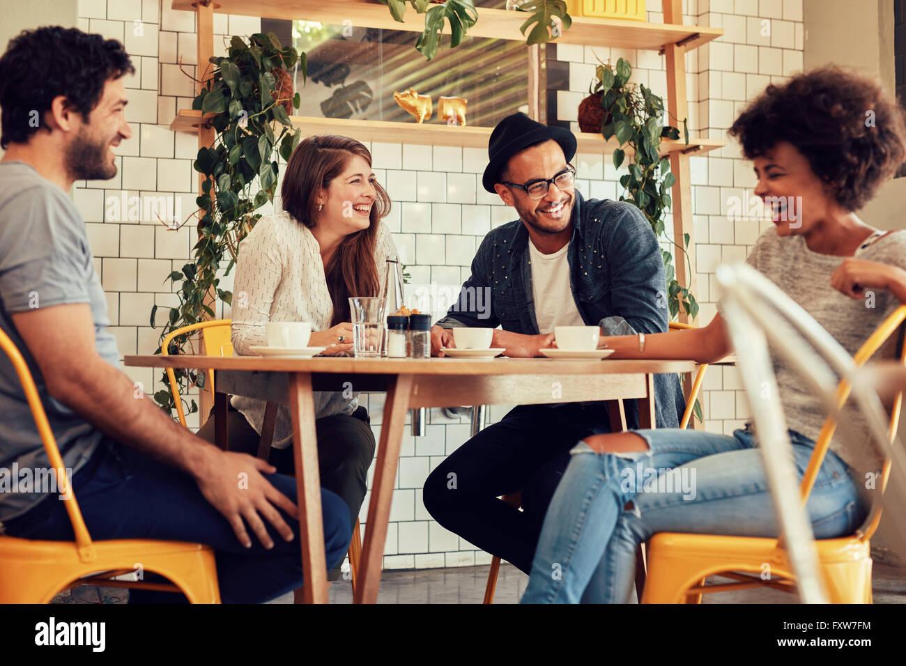 Junge Menschen, die eine tolle Zeit im Café. Freunde, lächelnd und in einem Café sitzen, Kaffee trinken Stockbild