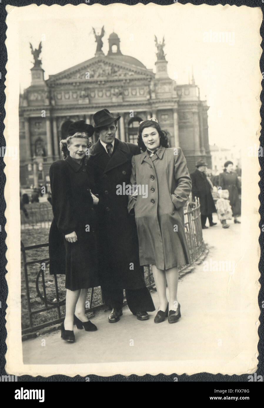 Ein Mann und zwei junge Frauen auf einem Hintergrund von dem Theater für Oper und Ballett, Lemberg, UdSSR. Stockbild