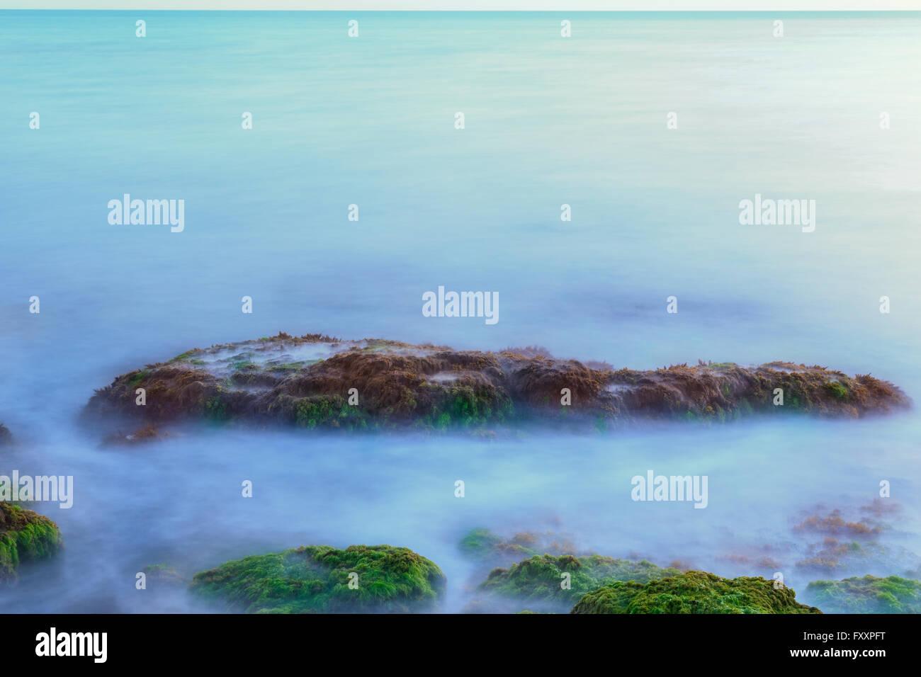 Ätherisch Langzeitbelichtung Schuss von Meereswellen und Felsen mit grünen und braunen Algen am Strand Stockbild