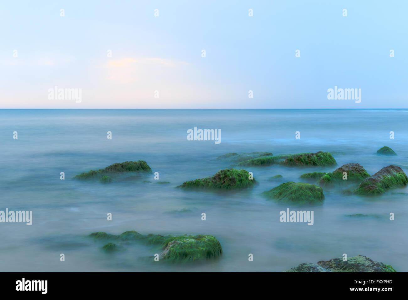 Ätherisch Langzeitbelichtung Schuss von Meereswellen und Felsen mit grünen und braunen Algen Stockbild