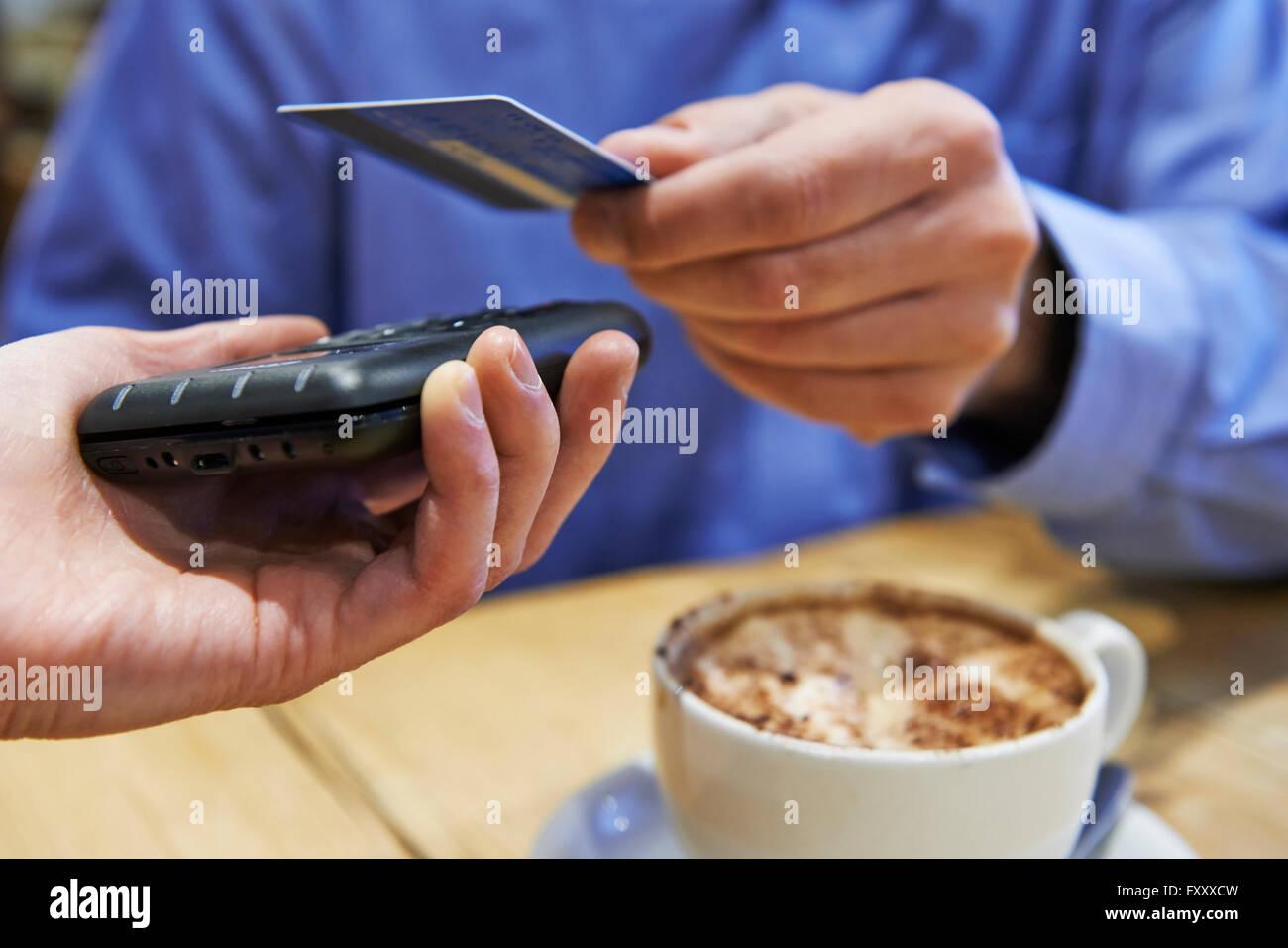 Kunden mit kontaktloses Bezahlen In Coffee-Shop Stockbild