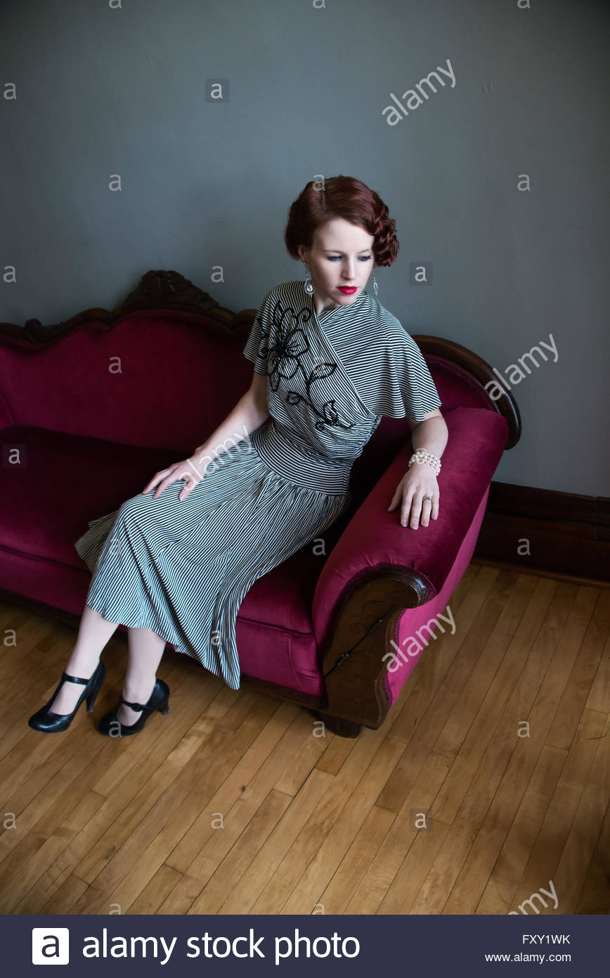 Frau im Jahrgang 1940er Jahre Kleid auf sofa Stockbild