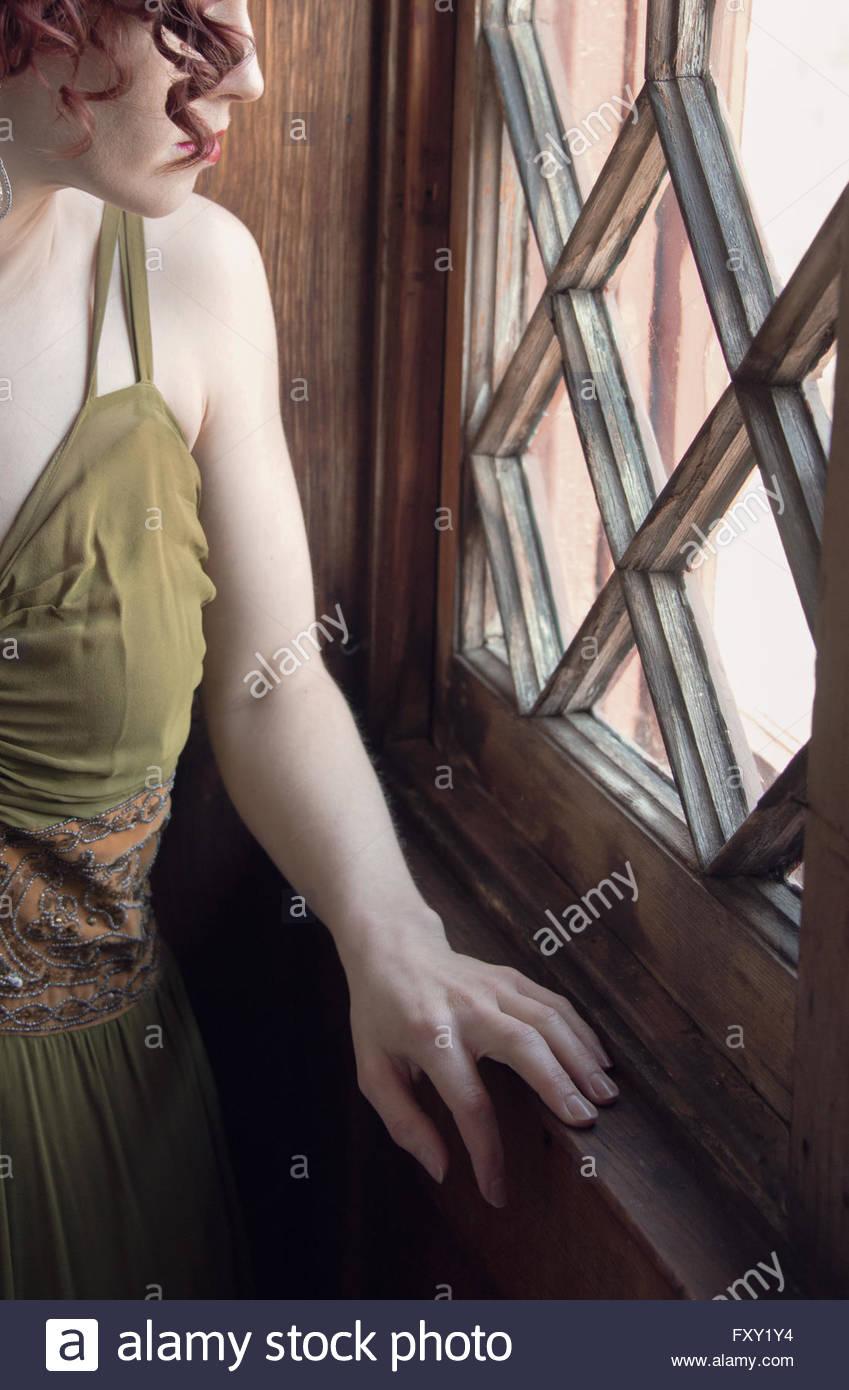 Frau im Jahrgang 1940er Jahre Kleid von Fenster Stockbild