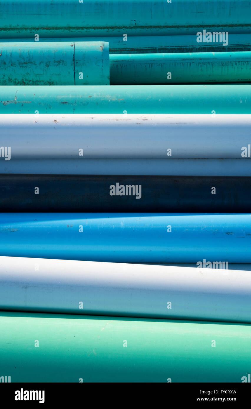 Auszug aus blauen, weißen und grünen Wasserleitungen gestapelt auf einer Baustelle an einem sonnigen Tag Stockfoto