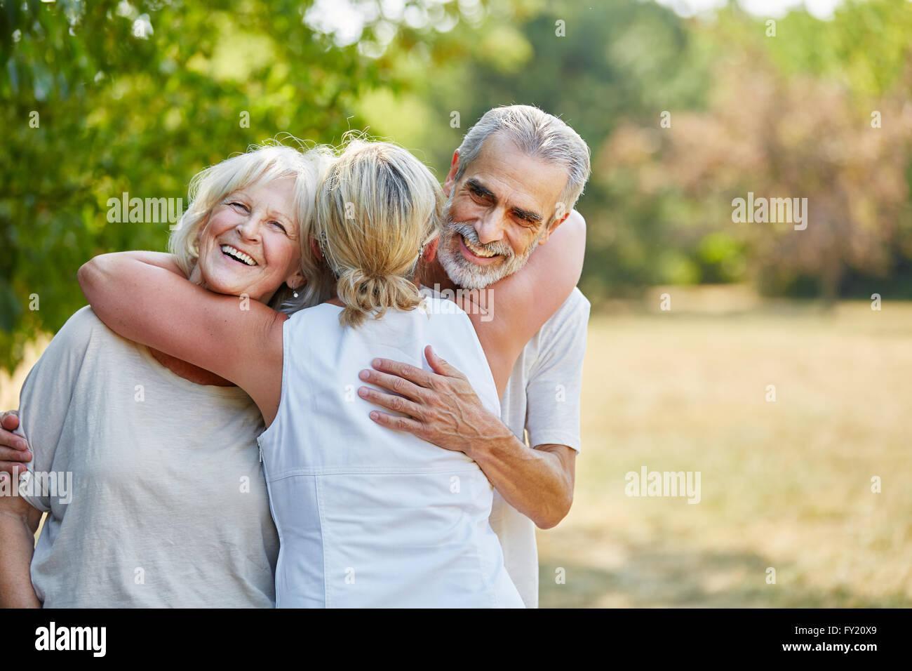 Glücklich Senioren Freunde umarmen einander im Garten im Sommer Stockbild
