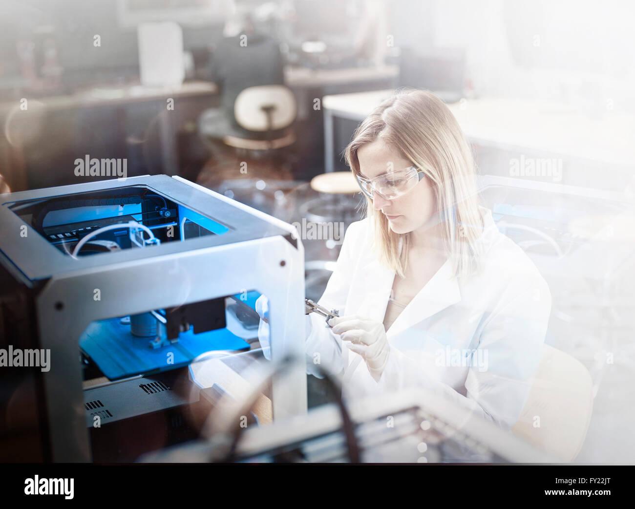 Weiblichen Techniker, 25-30 Jahre, im weißen Kittel und Schutzbrillen, Kontrolle der Druck eines 3D-Druckers, Stockbild