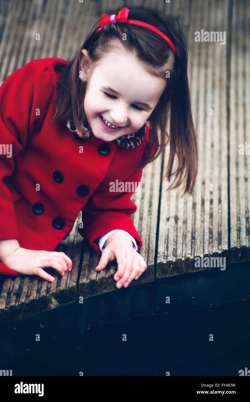 ein kleines Mädchen sitzt auf Holz allein und Lächeln Stockbild
