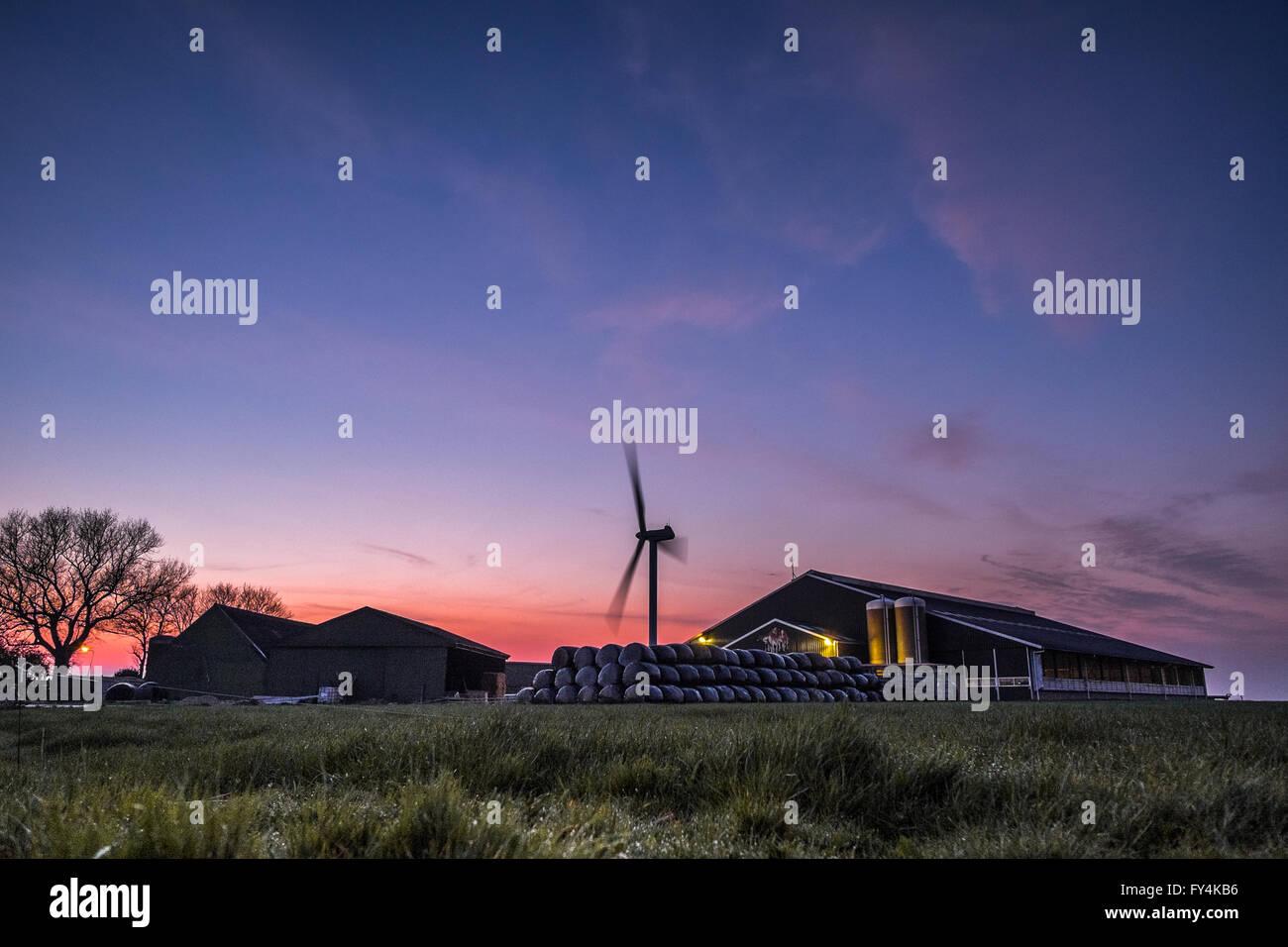 Ein angetriebene Windpark in Friesland erstrahlt in rot orange Leuchten der Sonnenuntergang als der Tag endet.  Stockbild