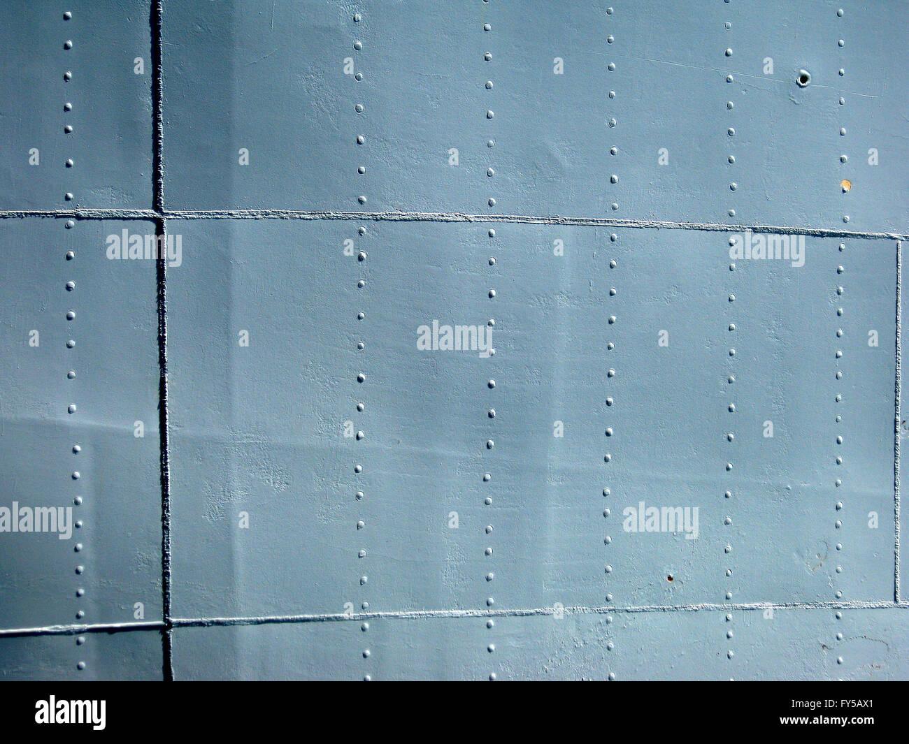 Detaillierten grauen historischen 2. Weltkrieg Schiff Metallwand mit Nähten und Nieten. mit einem Chip von Stockbild