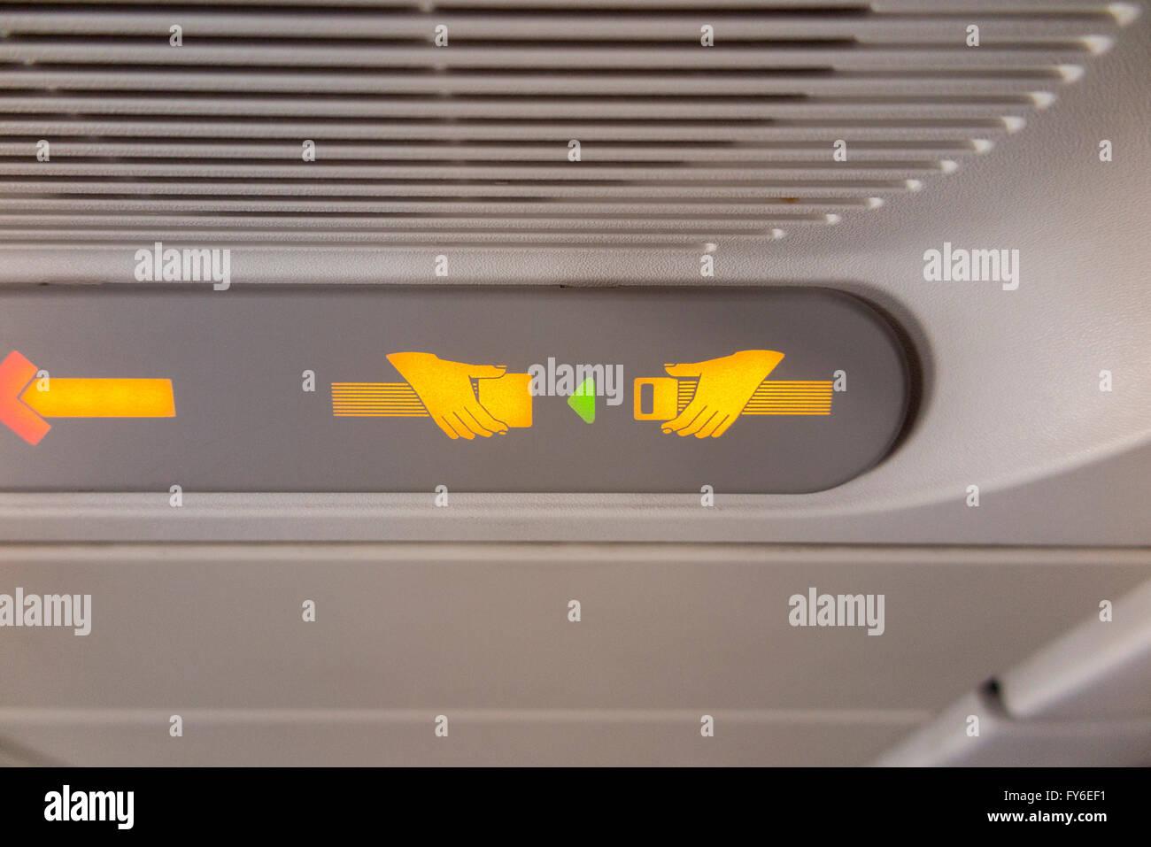 """Flugzeug """"Fasten Seat Belt / Sicherheitsgurt"""" Licht Zeichen leuchtet & beleuchtet während eines Fluges im Flugzeug Stockfoto"""