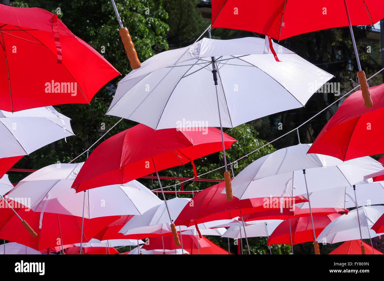 Bunte Schirme hängen über blauen Himmel. Rot und mit großen Sonnenschirmen auf den blauen Himmel. Stockbild