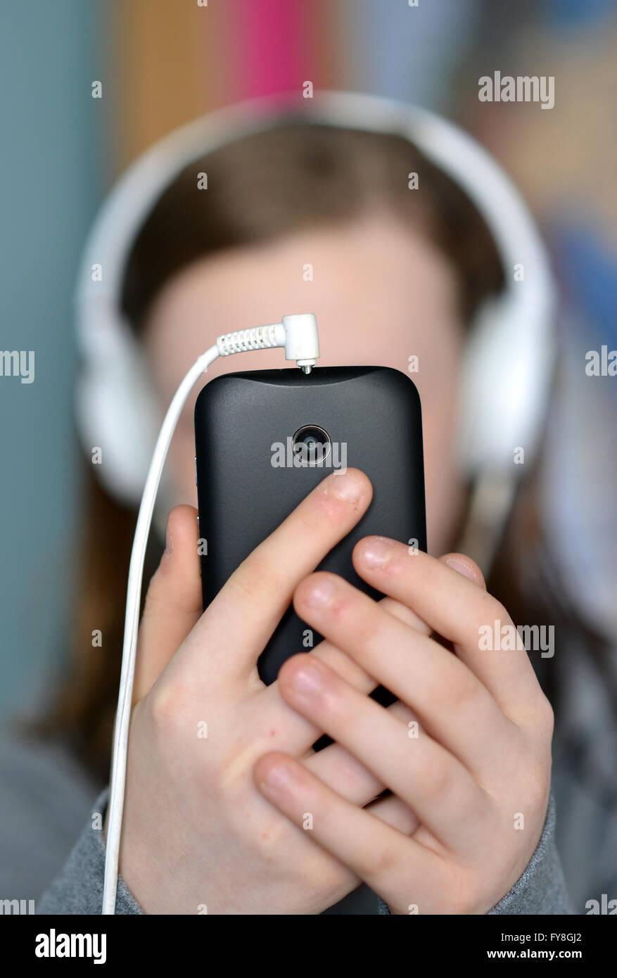 Teengirl mit Mobiltelefon (Handy) und Kopfhörer Stockfoto