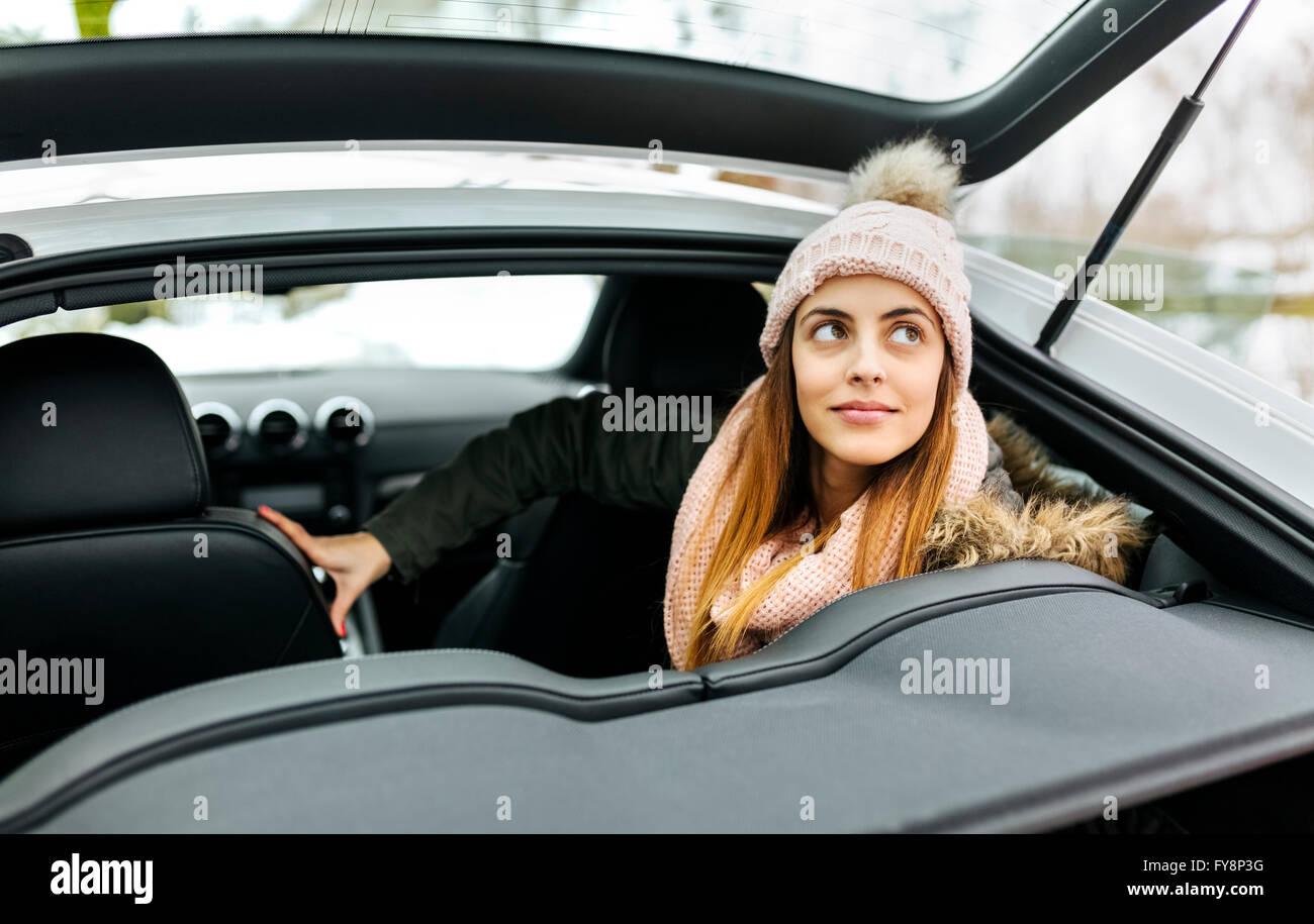 Portrait von junge Frau sitzt in einem Sportwagen Stockbild