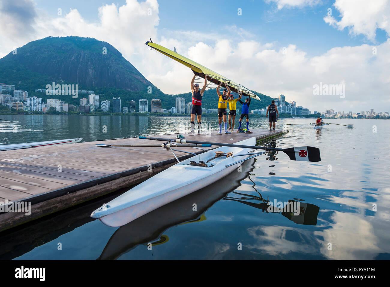 RIO DE JANEIRO - 1. April 2016: Mitglieder des Vasco da Gama-Ruderclub tragen ihr Boot am Lagoa Rodrigo de Freitas. Stockbild