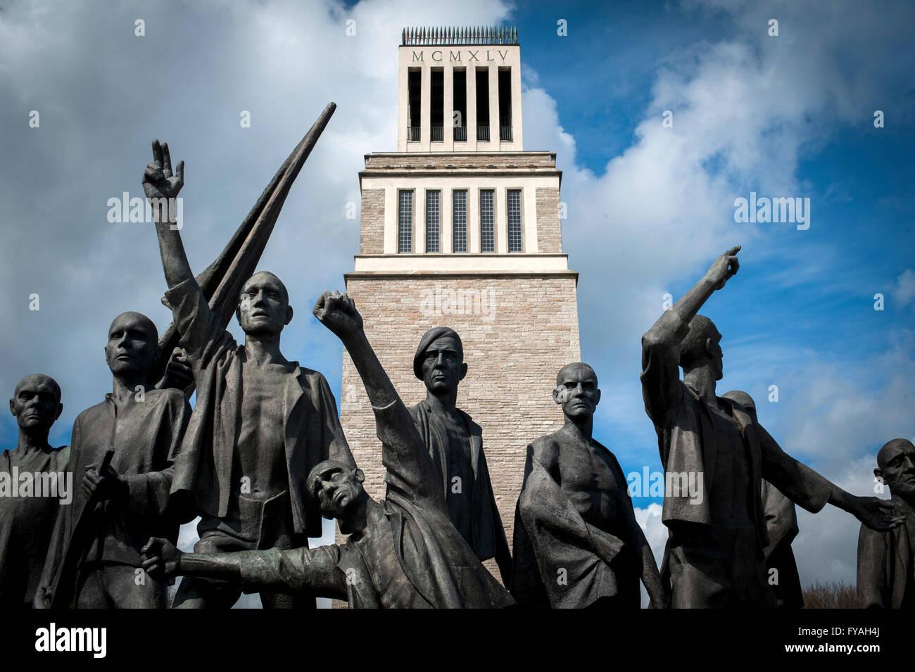 """Fritz Cremer-Skulptur der befreiten Häftlinge mit dem """"Turm der Freiheit"""" hinter in der Gedenkstätte Stockbild"""