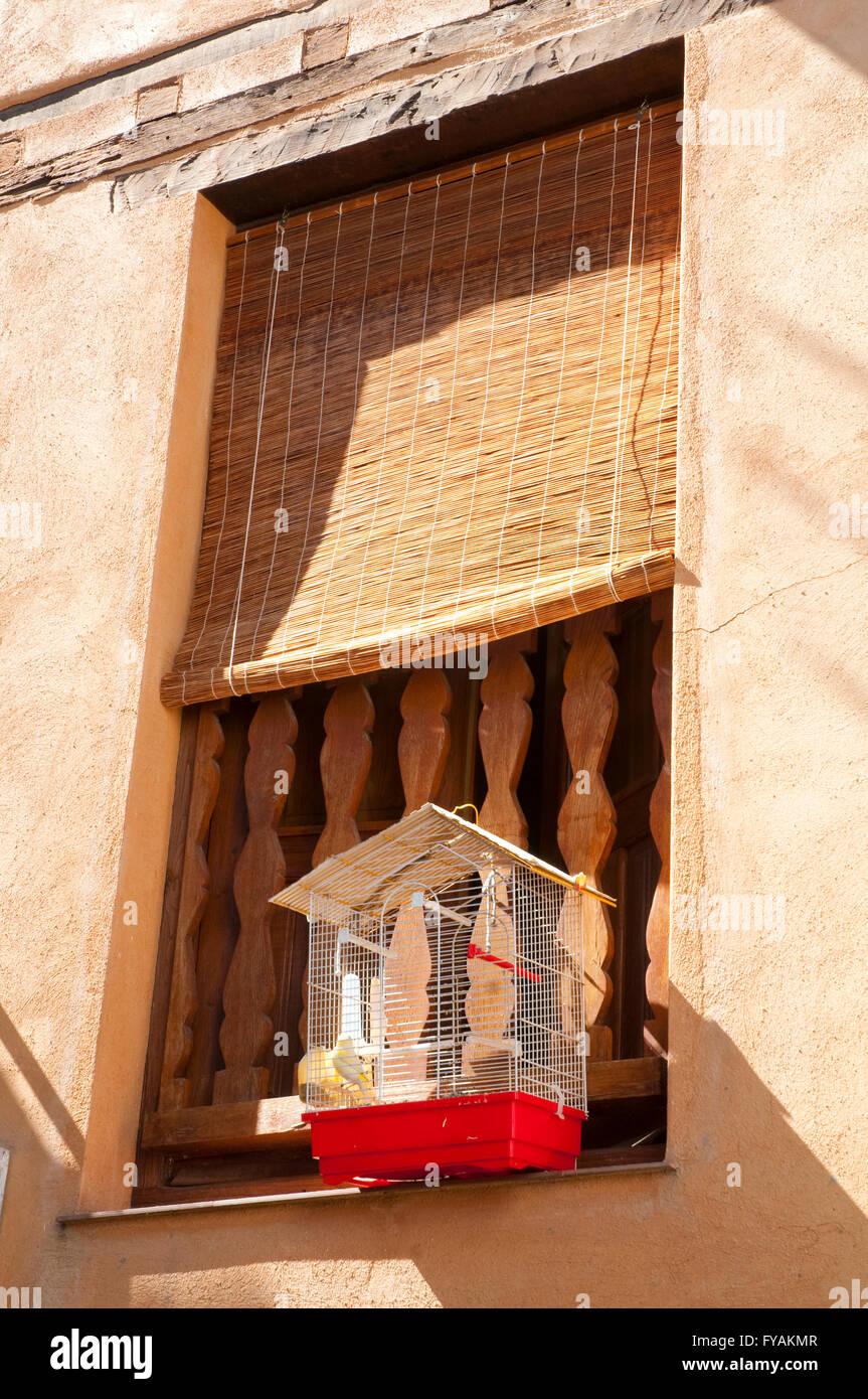 Fenster mit einen Kanarienvogel in einem Käfig. Hervas, Provinz Cáceres, Extremadura, Spanien. Stockbild